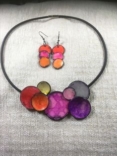 By Debby Wakley Premo polymer clay, alcohol inks, pastels. Disk necklace and earrings on a simple buna cord