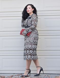 Girl With Curves blogger Tanesha Awasthi wears a lace midi dress, red clutch and ankle strap heels.