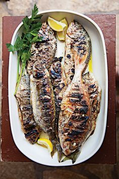 Whole Grilled Fish with Lemon (Riba na Rostilju): Seka Salamun, a home cook in Tisno, Croatia, uses olive wood to impart a mild smokiness to this grilled fish. Though delicious with just a squeeze of lemon, it also pairs beautifully with classic French fish sauces like beurre blanc, ravigoté, or tomato coriander broth. This recipe first appeared in our April 2014 issue with Brendan Francis Newnam's story Splendor of the Isles.