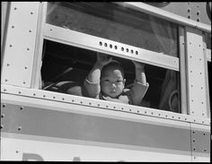 April 29, 1942 —San Francisco, California. A young evacuee looks out the window of bus before it starts for Tanforan Assembly center. Evacuees will be transferred to War Relocation Authority centers for the duration.