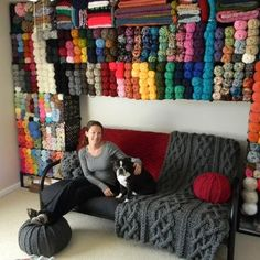 I wish I could have a room that looks like this, perhaps one day. I love that throw and the pouf. Not to mention the beauty of the well organized yarn on that wall.