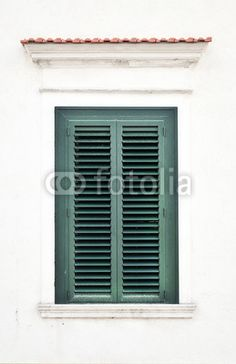Finestra chiusa con persiane verde su muro bianco