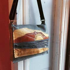 this unique messenger bag bears a sunset scene stitched in blocks to the front flap. the body of the bag is color-blocked in the same colors. large