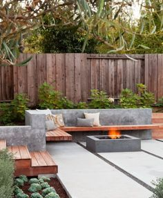 L-Shaped Wooden Seating with Concrete back and Square Fire Pit with Rock Fire Glass in Modern Patio Design Ideas
