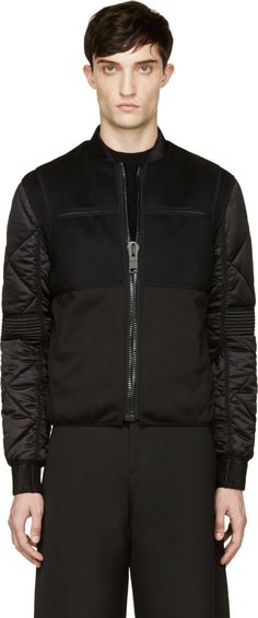 Long sleeve bomber jacket in black. Alternating textures throughout. Ribbed stand collar and sleeve cuffs. Layered panel at chest and upper back with openings at armscyes. Oversized zip closure at front. Slit detailing at upper chest. Quilted sleeves with flap detail at elbows. Welt pockets at waist. Fully lined. Tonal stitching.