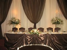 Chocolate Brown/Ivory Backdrop and head table decor. Chocolate brown satin wrap chair covers. Matching chocolate brown cake table
