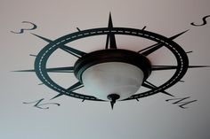 Neat idea to place a compass rose wall decal on the ceiling around a ceiling light. Adventure is out there!