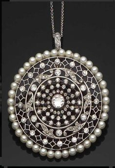 A belle epoque circular pendant Of openwork design set with a main circular-cut diamond to the centre within a frame of further circular-cut diamonds surrounded by pearls suspended by a diamond-set top loop from a tracelink chain