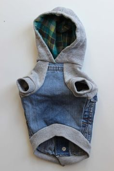 This dog jacket was upcycled from a Childrens Place denim jacket with snap closure, and a ladies Aeropostale hoodie. The grey hood is lined with a cotton flannel plaid of turquoise, charcoal grey and lime green (which looks super cute when peeking out from inside hood). The sweatshirt sleeves, while looking stylish, provide a little extra stretch and comfort for the dog wearing it. This jacket pulls over the head, and then snaps down the back. Original rib trim used at hem and sleeve cuffs…