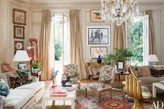 Between the French doors are a photograph by Bruce Weber and, below that, a painting by Yue Minjun; the curtains are of a Clarence House silk taffeta.