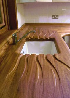 Beautifully carved bench top with integrated draining board. http://simonbirtwistle.co.uk/index.php/galleries/39-worktops | Kitchen