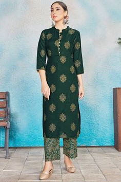 Elegance and charm is what you will exude once you get this dark green rayon trouser suit which will give a very sassy look. This chinese collar neck and 3/4th sleeve suit designed using foil print work. Along with rayon straight pants in dark green color with dark green chiffon dupatta. Straight pants has foil print work. #trousersuit #salwarkameez #malaysia #Indianwear #Indiandresses #andaazfashion Salwar Kameez, Churidar Suits, Kurti, Trouser Suits, Trousers, Pantalon Cigarette, How To Dye Fabric, Green Fabric, Indian Dresses