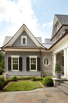 Grey shake siding, black shutters, white trim, stone & copper or bronze accents
