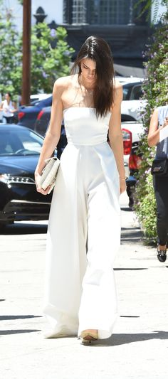 Kendall Jenner wears a strapless, wide-leg white jumpsuit with nude heels and a white cutch