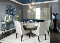 Contemporary dining room with a splash of blue, gray and a light colored rug…