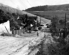 Two children walk up a dirt road in Chavez Ravine in 1950. Photo Leonard Nadel, courtesy of the Southern California Library for Social Studies & Research.