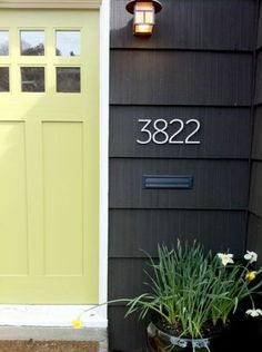 Traditional style blends beautifully with modern appeal in this example. Great soft lime front door color! The overall look with the black, wide horizontal siding and silver house numbers creates a stunning first impression.