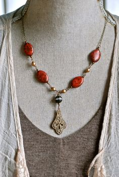 This is so lovely.. perfect for Fall and Winter!   features assorted glass beads,rhinestone bead,ornate brass etched pendant,antique brass chain