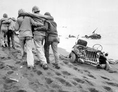 Navy corpsmen helped a wounded Marine to reach an aid station Iwo Jima February-March 1945. Note a crushed Jeep and submerged M4 Sherman tank.