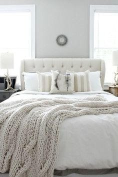 white bedroom with upholstered bed and chunky textured blanket
