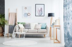 Paintings of cactus and hexagons hanging over a cozy sofa with many pillows standing next to a black lamp in living room interior Cozy Sofa, Blue Curtains, Diy House Projects, Simple Projects, Diy Home Improvement, Living Room Interior, Decorating Your Home, Mid-century Modern, Modern Houses