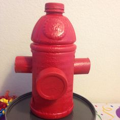 Paw Patrol birthday centerpiece! Diy w/ an applejuice bottle, 1 toilet paper roll and a can of bubble tape gum! Hot glue and spray paint an viola! Instant fire hydrant!