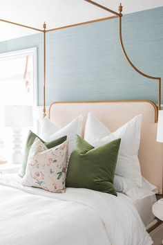 Blue Sisal Bedroom Wall. Gorgeous bedroom features upper walls clad in Thibaut Shang Extra Fine Sisal Mineral Wallpaper and lower walls clad in wainscoting painted Sherwin Williams Extra White lined with a gold leaf canopy bed with headboard and footboard Frontgate Park Lane Canopy Bed dressed in moss green velvet pillows flanked by a Noir Giza Dresser to the left and a Noir 9 Leg White Wash Side Table to the right along with Arteriors Wheaton White Table Lamps. #Bedroom #BlueBedroom #Sisal…