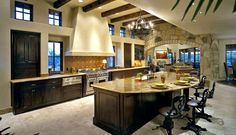 Luxury kitchen interior design in open living space with elevated ceiling.  Large island is semi-circular with seating on the outside facing the kitchen.