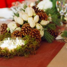 Centerpiece idea with flowers in your colors, pine or other woodsy foliage, pine cones, moss and votives.