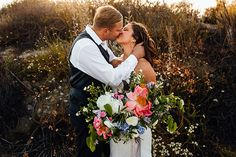 Modern boho styled shoot bride strapless a line gown with a sweetheart neckline and groom navy tuxedo with white dress shirt and no tie with matching vest and no jacket holding white and pink floral bridal bouquet