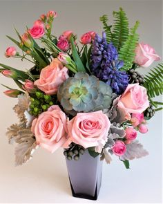 Boutique Blooms-Mixed Pastel shades of roses, tulips , Hyacinth and modern succulents nested high quality lavender glass vase, this simply elegant design is a reflection of Spring textures and colors. Truly a one-of-a-kind design. #StadiumFlowers #EverettFlowers #AdministrativeProfessionalsWeek
