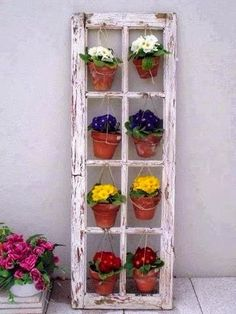Old window frame graced with hanging flower pots