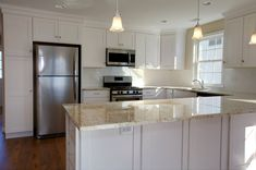 Beach house kitchen featuring classic white cabinetry and Colonial Gold granite countertops.  The backsplash is a simple white subway tile.  Kitchen by Stoneshop from Cherry Hill, NJ.