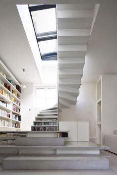creative use of stairs as storage and design element, loft style, sky light windows and stairs Love the bookshelf wall and use of stairs