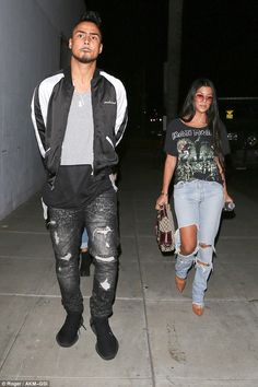 His and hers: Quincy, meanwhile, stepped out in a similar pair of dark acid wash distressed jeans that he paired with a monochrome bomber jacket and colour block tee underneath