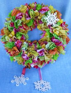 This is the fabric square wreath I made for my door for Christmas 2011- 3 1/2 squares of fabrics in red, hot pink, lime green, yellow-fabric is punched into Styrofoam wreath base with a bamboo skewer, painted & glittered plain wooden snowflakes, glued one snowflake to corkscrewed pipe cleaner & poked end of pipe cleaner into base so snowflake could float above fabric, glued other snowflakes to ribbons & glued them to back of wreath - only cost was for wreath form as I already had other stuff