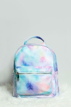 A woven mini backpack featuring an allover tie-dye print, top handle, a zippered top, adjustable shoulder straps, a front zippered pocket, and two interior slit pockets. Pastel Backpack, Mini Backpack Purse, Leather Backpack, Book Bags, Tie Dye Backpacks, Shoulder Straps, Kipling Backpack, Galaxy Backpack, Latest Sunglasses