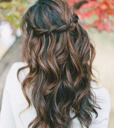Pour dynamiser ces cheveux longs légèrement ondulés, le coiffeur a joliment tressé quelques mèches qu'il a positionnées à l'horizontale à l'arrière de la tête de la jeune femme. De plus, il a savamment ajouté des mèches brunes pour éclaircir la chevelure.