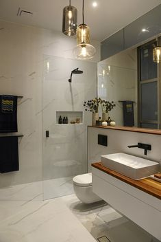Master Bath - Marble-look floors & walls, white floating vanities, wood countertops, white vessel sinks