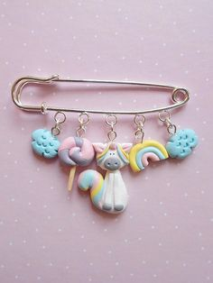 Unicorn pin made from polymer clay. With unicorn, lollipop, rainbow and fluffy clouds. The metallic support measure 6 cm and the each charm maximum lenght is 2 cm. The charms are completely made out of polymer clay, without using molds of forms. ❀ Because i make everything by hand, the item