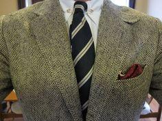 Light grey tweed jacket, white shirt, navy tie with white stripes, navy pants
