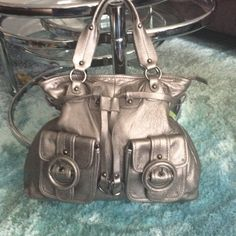 Elliott lucca hand held handbag silver Hand held  hand bag with cinched belting and 2 exterior pockets with covered leather buckles. 3 interior pockets. Elliott Lucca Bags Satchels