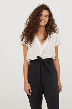 White/dotted. V-neck blouse in satin with cap sleeves. Box pleat at front, gathered yoke at back, and rounded hem. Slightly longer at back.