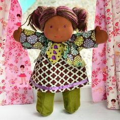 This is Mya, a Classic Bamboletta from the March 9, 2012 upload. She has dark skin, long hair made with mohair and wool yarns in a brown color with multi-colored fairy bits and violet eyes. She is wearing the pictured outfit, underpants and wool felt shoes.
