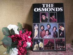 """The OSMONDS Concert Program from 1982 14"""" x 9"""" Souvenir Program Black cover with blocks of color photographs 20 interior pages with black and white photos and narrative Color photo centerpiece - famil"""