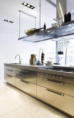 Keuken van Arclinea met industriële uitstraling. Deze industrieel ogende keuken van Arclinea heeft een lager gelegen kookplaat waardoor je beter zicht in de pannen hebt. De afzuigkap zorgt er niet alleen voor dat nare luchtjes uit de keuken verdwijnen, hij biedt ook nog eens goede verlichting op het hele werkblad. Daarnaast kun je er de kookartikelen op plaatsen die je regelmatig gebruikt. Arclinea, foto Abe van Ancum