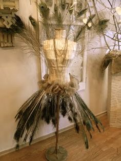Dress form covered in peacock feahers