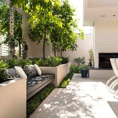 Outdoor sitting area against exterior wall -- abundant greenery softens concrete, symmetry creates balance.