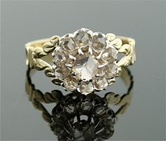 Antique Engagement Ring  This two tone Victorian diamond ring features rose cut diamonds in a flower pattern...too wonderful! The thin band has elegant side details. Quite a piece of history to own!  Original Victorian  11 Rose Cut Diamonds (0.75 cts, H-K/SI-I)  14k White and Yellow Gold  Size 6  *Center diamond has a small eye visible inclusion    $3295.00
