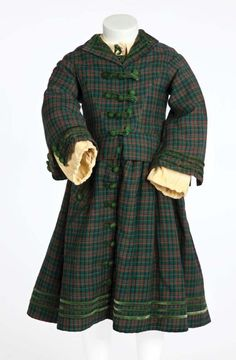 "Shirley Temple ""Virginia Cary"" green plaid period dress with jacket from The Littlest Rebel. (TCF, 1935) Green plaid period dress with matching jacket. The dress has handwritten ""Shirley"" and stamped 5""130 2 27 7 3904."" Jacket has no label. Worn by Shirley Temple as ""Virgie"" singing ""Polly Wolly Doodle,"" visiting her father in jail, tap dancing on the sidewalk, and visiting the President at end of film in The Littlest Rebel."